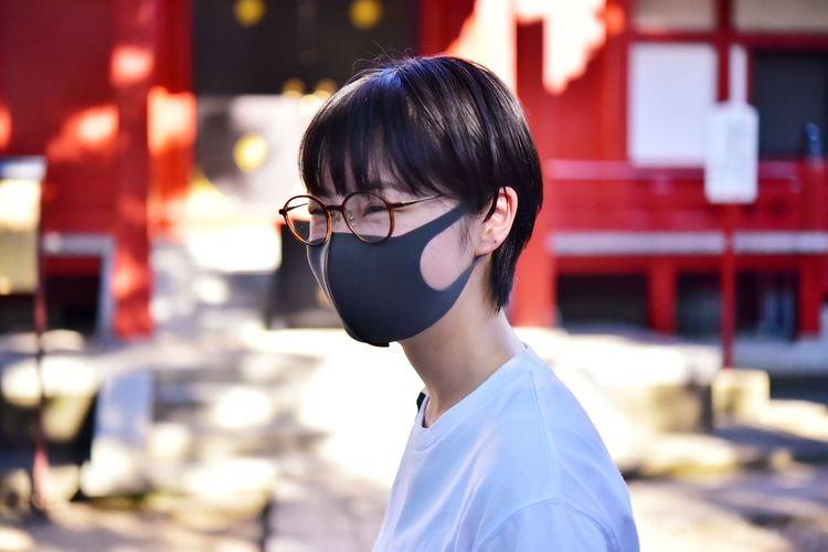 Close-up of woman wearing mask looking away standing outdoors