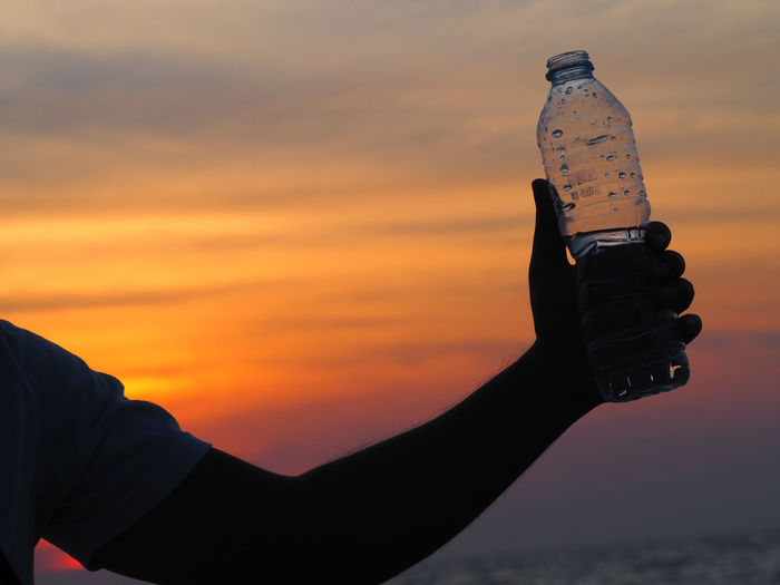 Cropped Hand Of Man Holding Water Bottle At Beach During Sunset