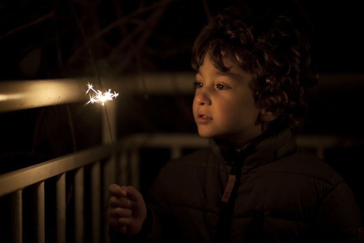 Portrait of boy looking away at night