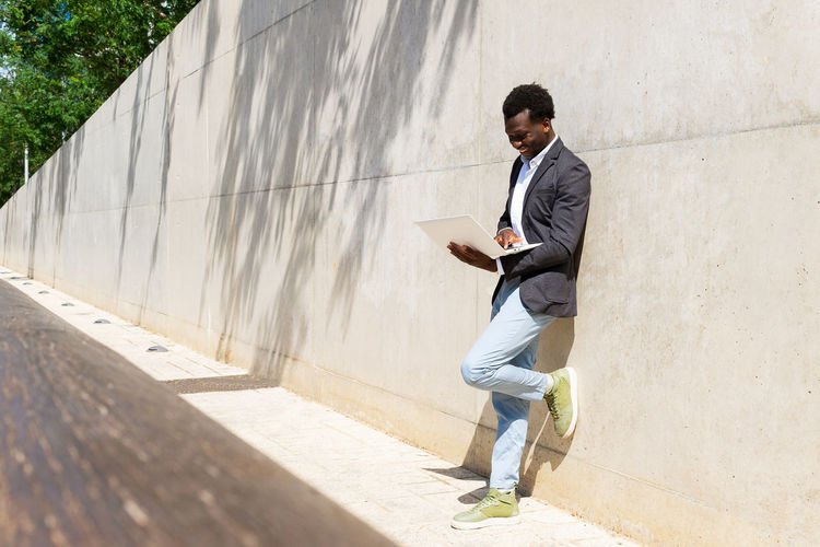 Young man using mobile phone while standing on wall