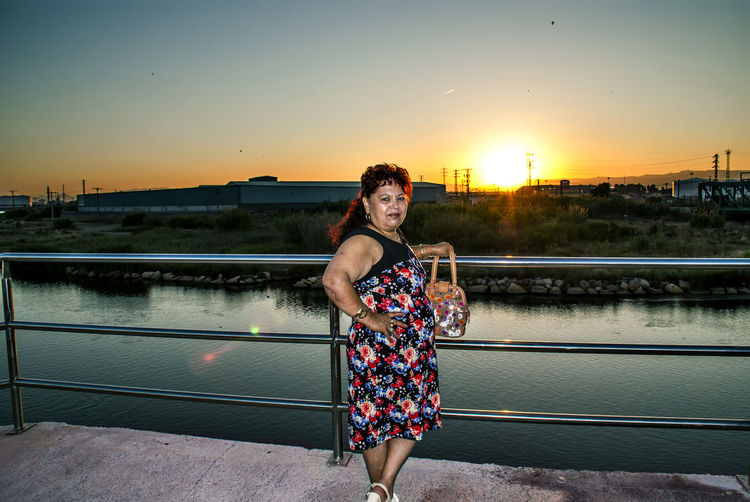 Portrait of woman standing by railing against river and sky during sunset