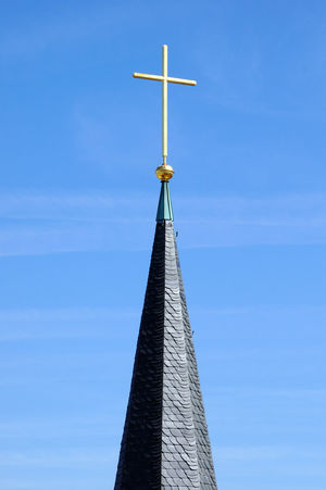 The spire of the Collegiate Church of Stuttgart. The covered with slate spire is topped by a golden ball on the projects the great golden cross in the sky. Turmspitze eines Turms der Stiftskirche Christian Church Cross Faith Gold Golden Steeple Symbol Tourism Tower Towers