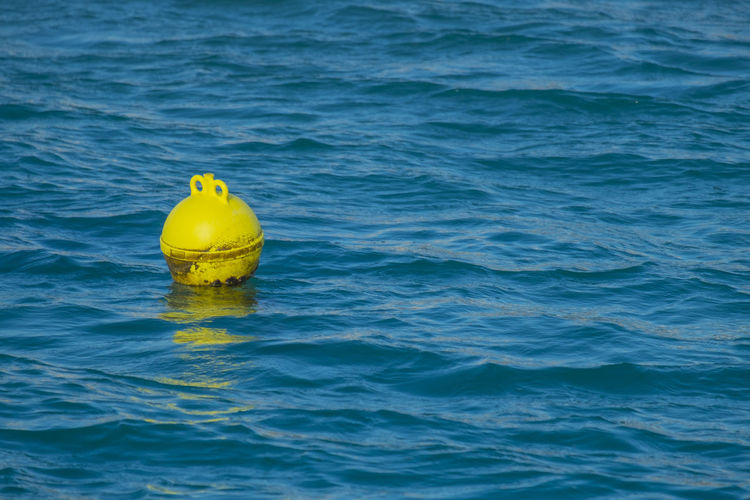Yellow marine signal buoy in the water