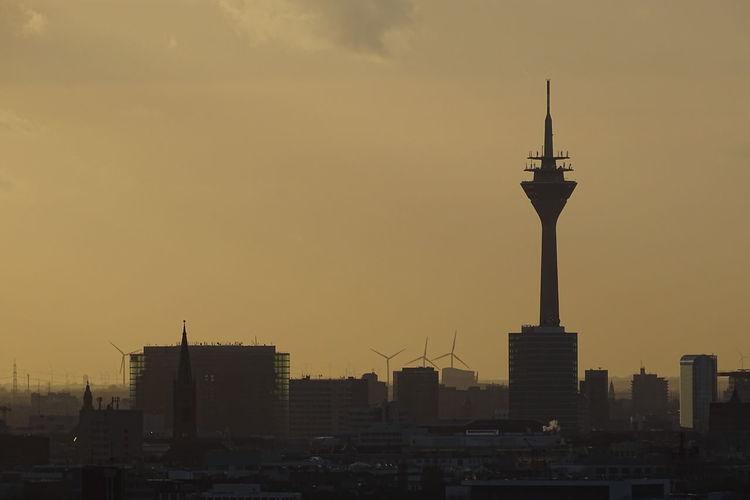Rheinturm And Buildings Against Sky At Sunset