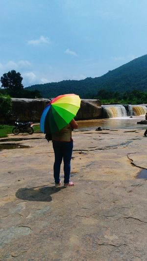 A Lady Under Umbrella Watching The Falls