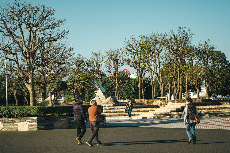 Rear view of men walking on sidewalk in city against sky