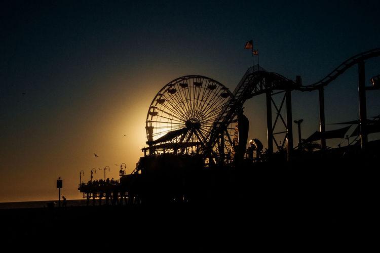 Silhouette Ferris Wheel At Beach Against Clear Sky