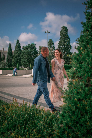 Full length of couple walking against trees