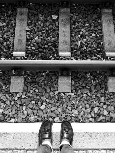 Low section of man standing on railroad station