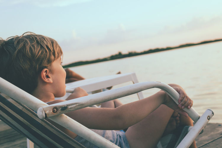 Small boy relaxing on a pier at sunset.