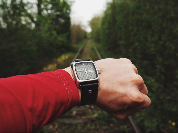Cropped Hand Of Person Wearing Wristwatch On Railroad Track