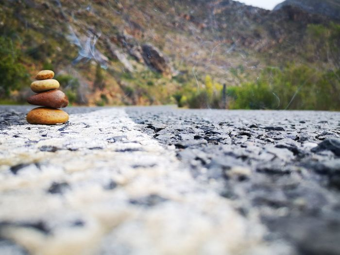 Close-up of stones stacked on road