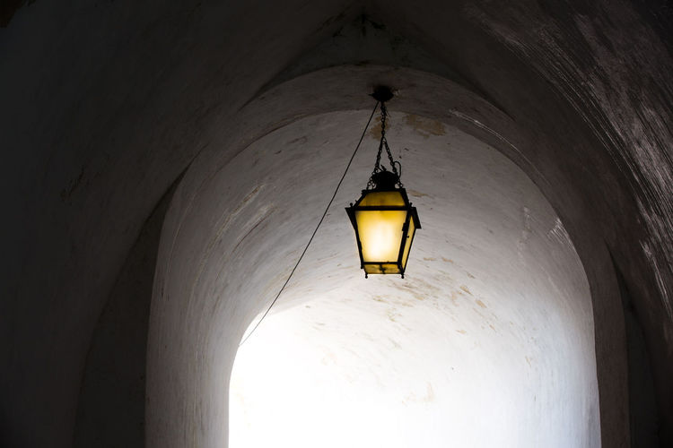 Arch Architecture Building Built Structure Ceiling Electric Lamp Electric Light Electricity  Grey Hanging Illuminated Illumination Indoors  Light Light - Natural Phenomenon Light Fixture Lighting Equipment Low Angle View No People Old Pendant Light Tunnel Wall - Building Feature Yellow