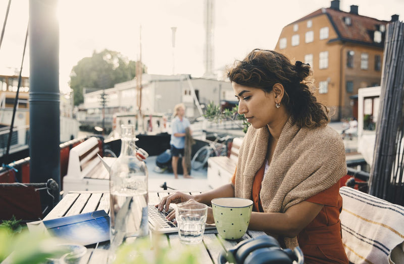 Young woman looking up while sitting on table in city