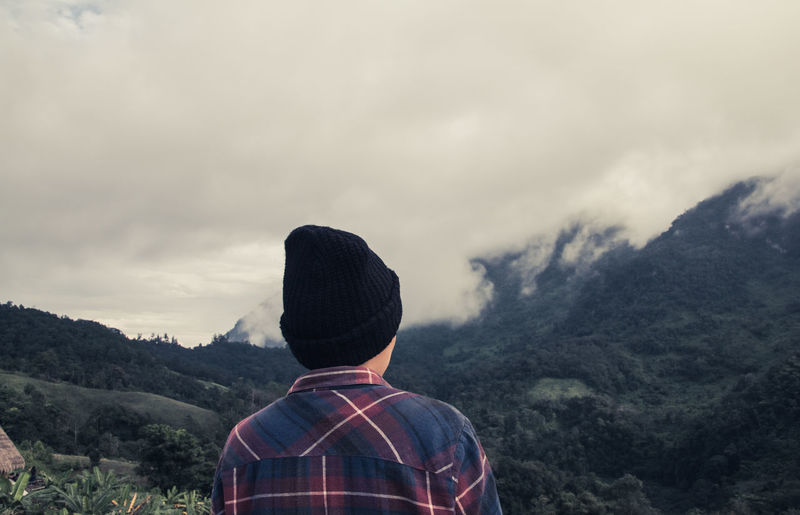 Rear view of man looking at mountains while hiking in forest