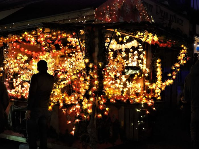 Rear view of man standing at illuminated market stall at night during christmas