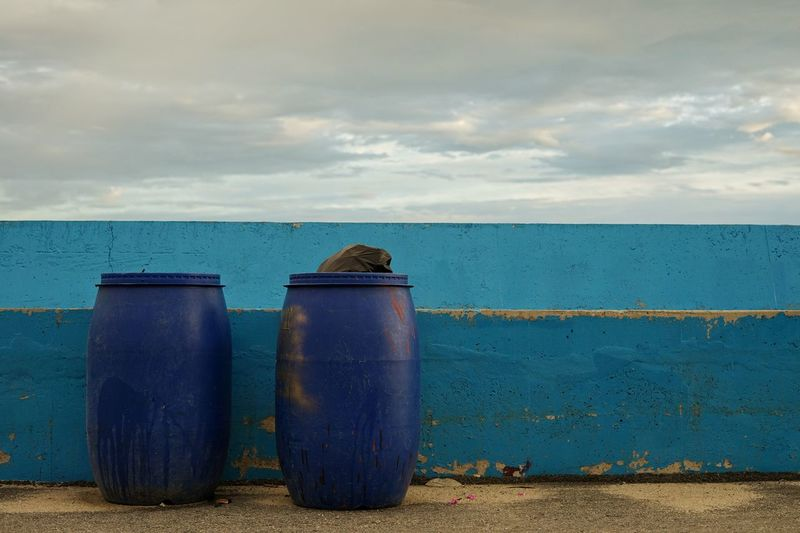 Metallic structure on sea shore against sky with the garbage bins.
