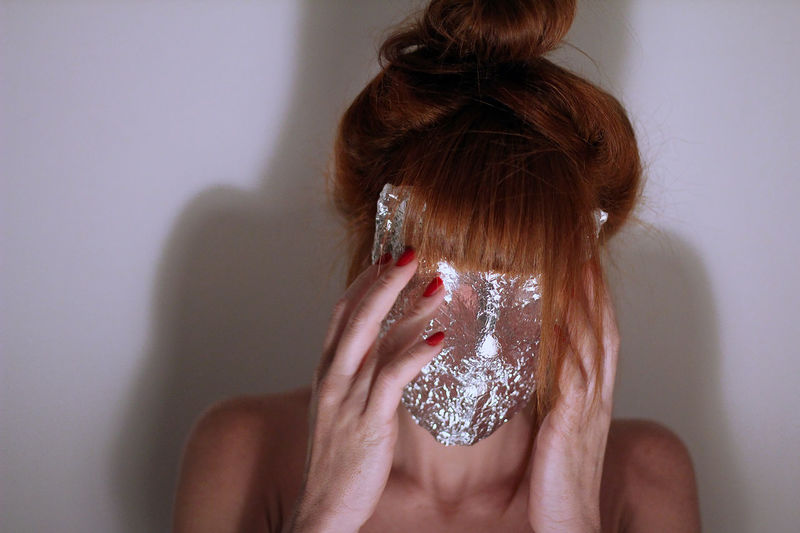 Close-up of woman covering face against white background