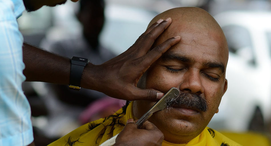 Cropped Image Of Barber Shaving Mustache Of Customer