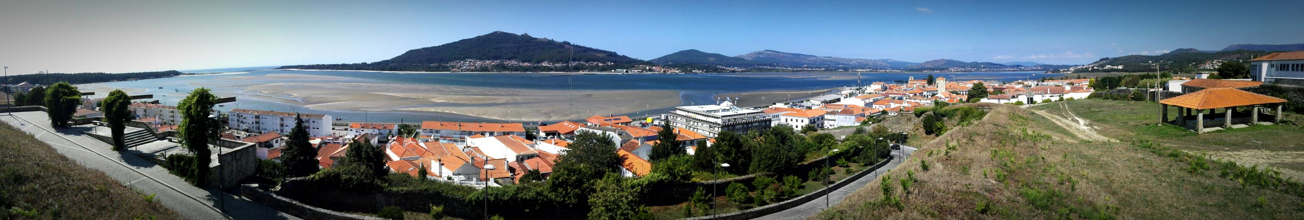 sea, beach, mountain, building exterior, clear sky, water, built structure, architecture, panoramic, high angle view, sand, coastline, town, shore, blue, large group of people, incidental people, horizon over water, house, sky