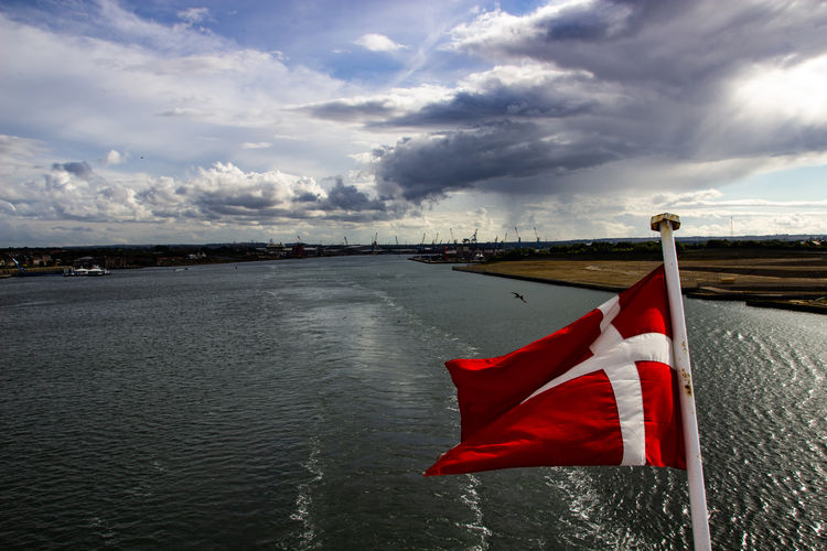Red flag on river against sky