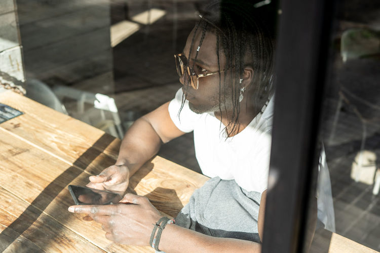 Man holding mobile phone while sitting on table