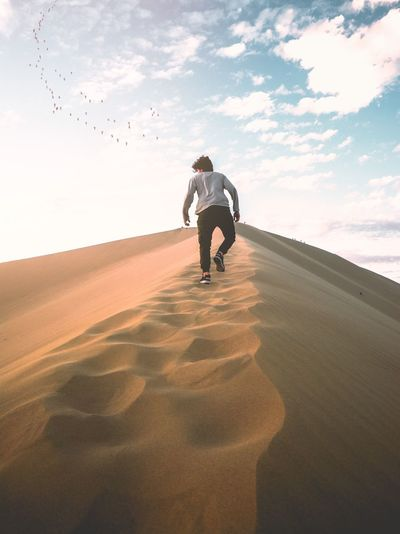 Walking on the sand Sunet Huacachina Peru Dune Sky One Person Real People Land Lifestyles Leisure Activity Nature Cloud - Sky Beauty In Nature Full Length Sand Casual Clothing Landscape Sunlight Day Men Sand Dune Plant Tranquility Outdoors