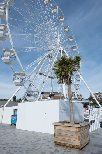Low angle view of ferris wheel by sea against sky