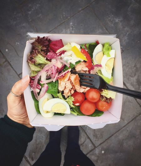 High angle view of woman holding fresh salad and smoked salmon