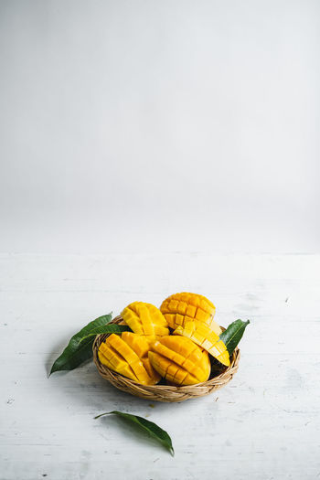 Mango in a basket Food And Drink Freshness Food Healthy Eating Studio Shot Yellow Copy Space White Background Wellbeing Indoors  Still Life Vegetable No People Table Close-up Fruit Green Color Nature Beauty In Nature White Color Temptation