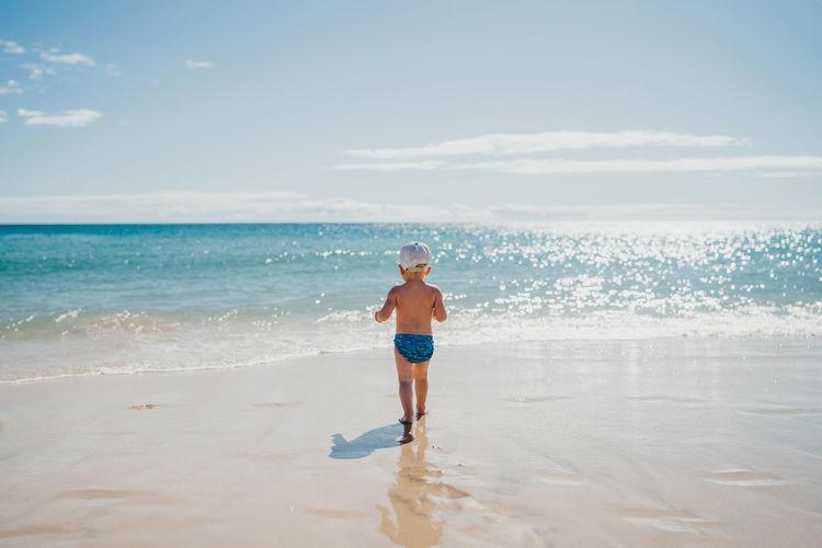 Full length of shirtless boy on beach against sky