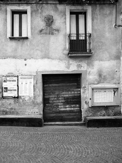 Iron gate, windows and bulletin board Black & White Bulletin Board Iron Gate Italia Old Town South Italy Architecture Balcony Black And White Black And White Photography Building Exterior Built Structure Calabria No People Outdoors Verbicaro Window Windows