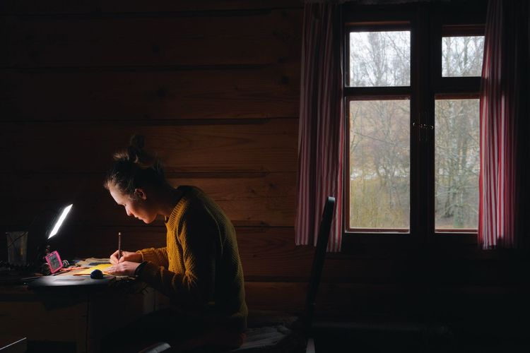 Side view of woman writing on table by window in log cabin
