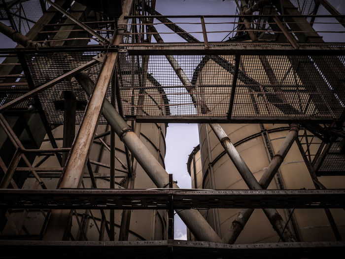 Low angle view of metallic structure by silos