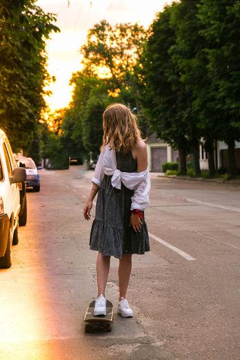 Millennial woman in dress riding a skateboard on street. skater girl on a longboard. cool female