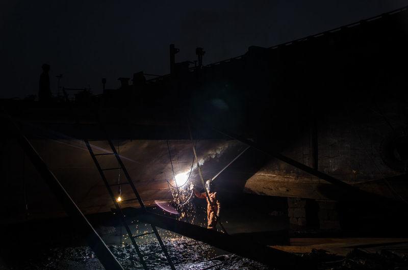 Welder working at ship yard at night