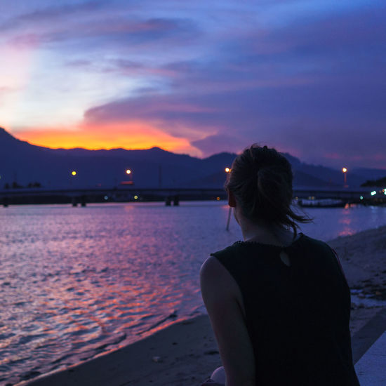 Beauty In Nature Cloud - Sky Illuminated Leisure Activity Lifestyles Nature Night One Person Outdoors People Real People Rear View Scenics Sea Silhouette Sky Standing Sunset Water Women Young Adult Young Women