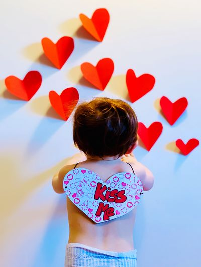 Rear view of baby boy with kiss me text standing by heart shape on wall