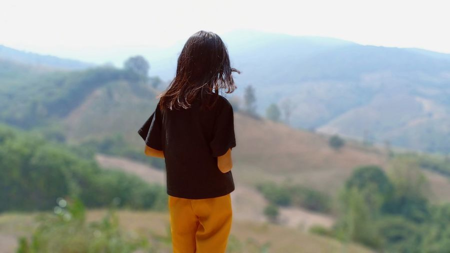Rear view of teenage girl standing against mountains