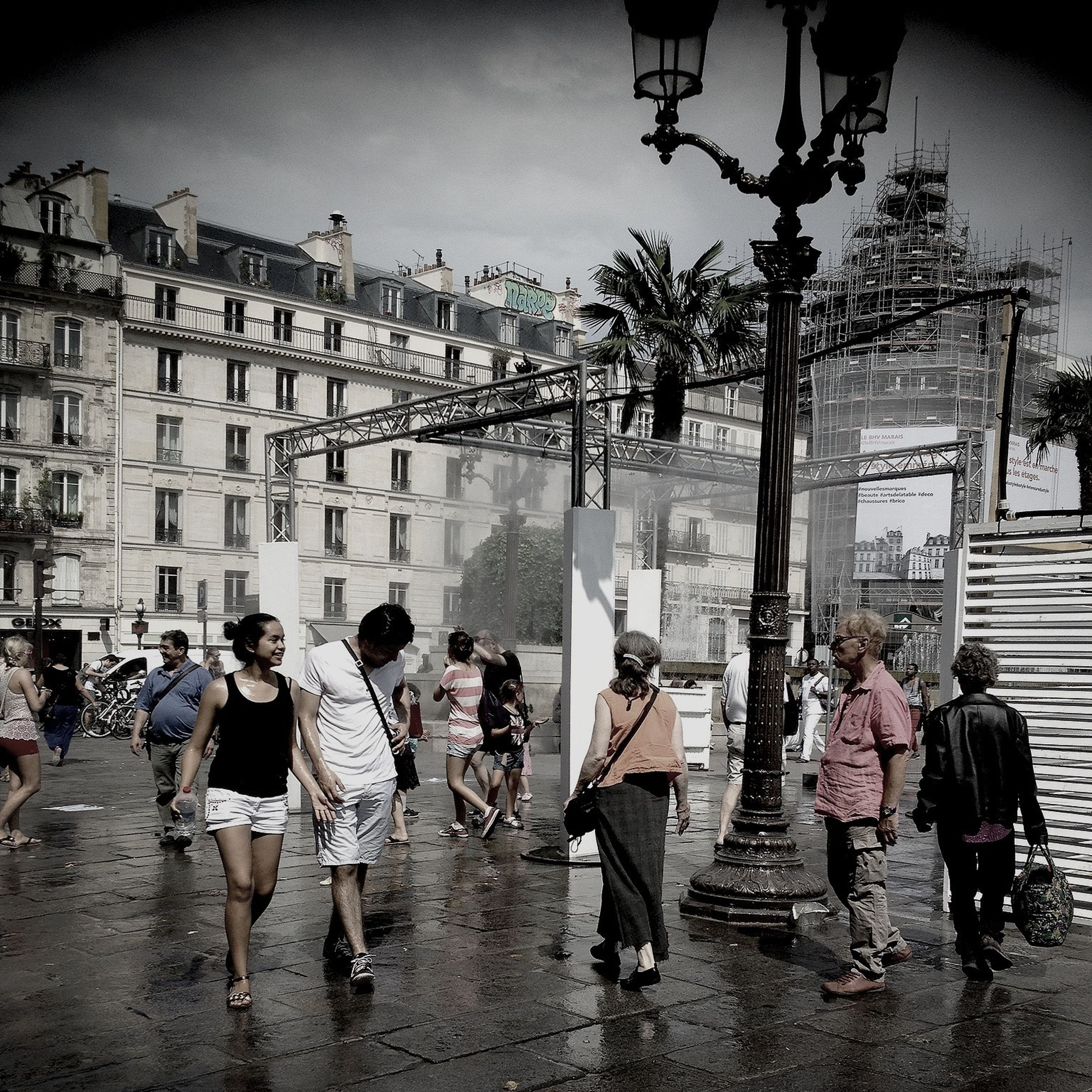 large group of people, men, person, lifestyles, building exterior, architecture, walking, built structure, street, city, leisure activity, city life, mixed age range, umbrella, crowd, water, togetherness, full length, casual clothing
