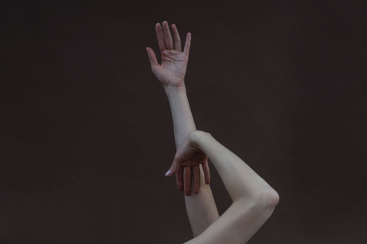 Midsection of woman with arms raised against black background