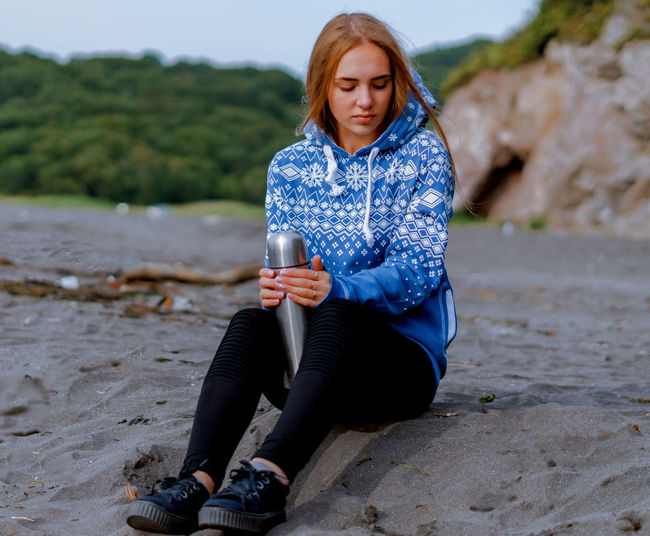 Young woman holding insulated drink container while sitting at beach
