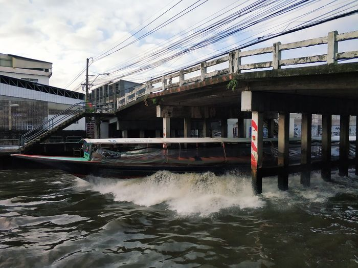 Speed Boat passes under the bridge Bangkok Transportation Speedboat River Canal Water Nautical Vessel Sky Architecture Building Exterior Built Structure Cloud - Sky Boat Water Vehicle
