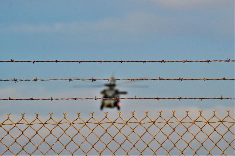 Chainlink fence against clear sky with helicopter