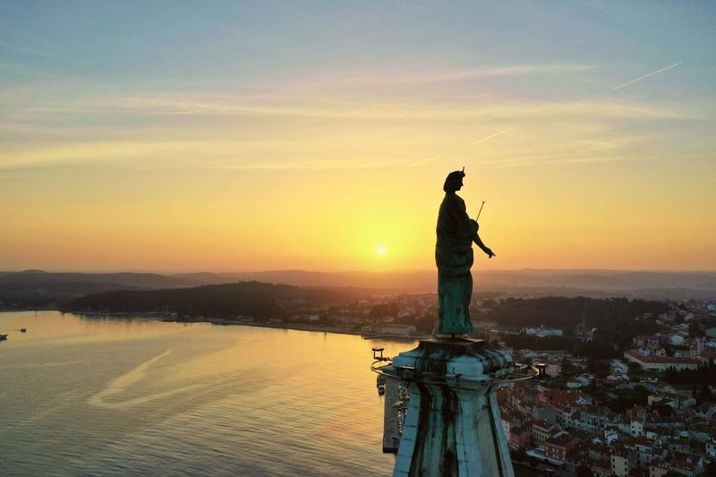 Statue of woman standing by sea against sky during sunset