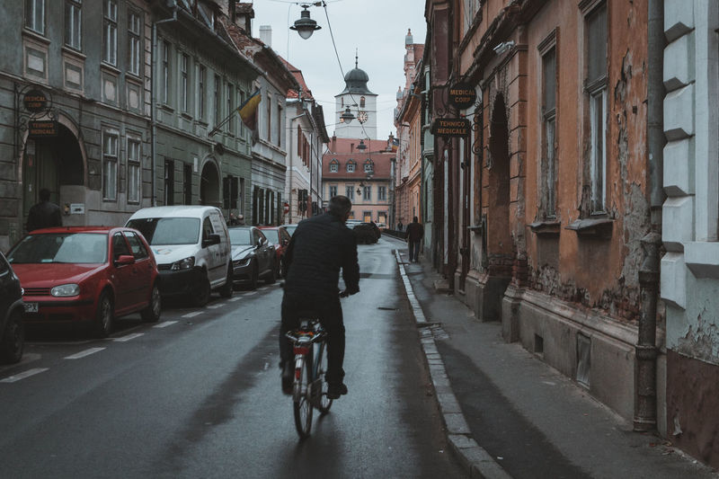A man on a bicycle rides through the old streets of Sibiu Romania. - IG: @LostBoyMemoirs - IG: @LostBoyMemoirs Streetwise Photography Steetphotography Street Photography The Week on EyeEm Best EyeEm Shot My Best Photo People People Watching People Photography people and places Bicycle The Way Forward Lifestyles Real People Architecture Riding Residential District The Art Of Street Photography