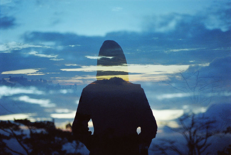 Double exposure of person standing against sky during sunset