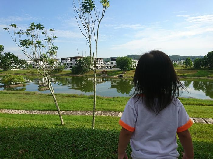 Rear view of girl standing on field against sky