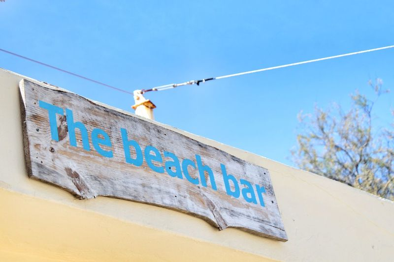 Beach bar sign Wooden Rustic Beach Words In The Wild Words Beach Bar Sign Blue Text Low Angle View Day No People Outdoors Built Structure Sky