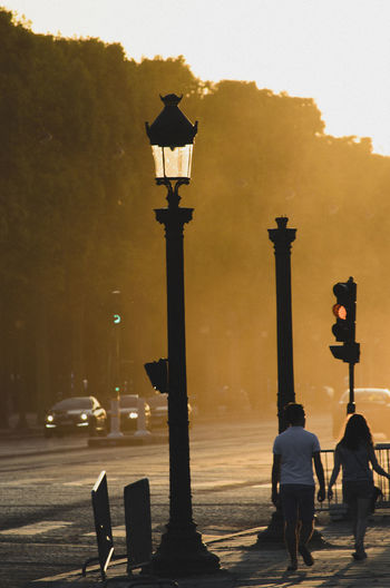 Rear view of couple walking by gas light on sidewalk during sunset